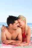 Geliebte, die sich auf dem Strand hinlegen stockfoto