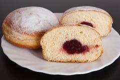 Gelieren Sie gefüllte Donuts auf weißer Platte auf schwarzem hölzernem Hintergrund Lizenzfreie Stockfotos