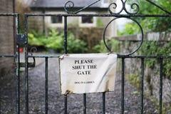 Gelieve te sluiten het poortteken bij ingang aan woontuin stock fotografie