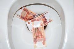 Gelijk geld in het toilet Stock Fotografie