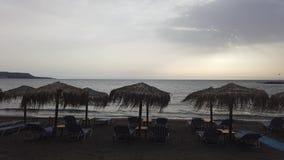 Gelijk makend op het strand met paraplu's en zitkamerstoelen, wind en golven stock videobeelden