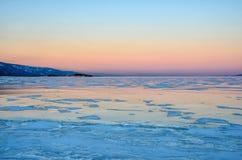 Gelo azul do lago Baikal sob o céu cor-de-rosa do por do sol fotos de stock royalty free