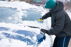 Gelo de raspagem do homem fora do carro imagens de stock royalty free