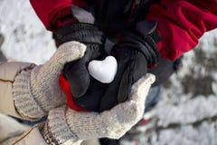 Gelo sob a forma do coração em suas mãos Fotos de Stock Royalty Free