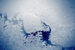 Gelo sul vetro su fondo blu immagine stock