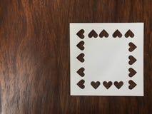 Gelocht in der Herzform des leeren Papiers des weißen Quadrats auf dunkelbrauner hölzerner Tabelle Stockbild