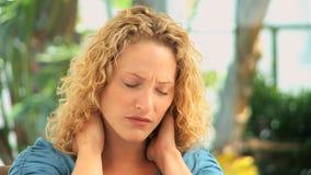 Gelockte behaarte Frau, die Nackenschmerzen hat stock footage
