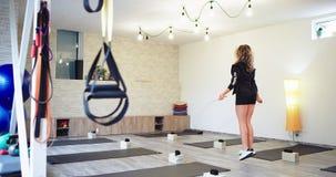 Gelockte blonde Dame in einem Wellnessstudio, auf das Seil springend, das Video vom hinteren Gesundheitslebensstilkonzept nimmt