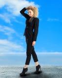 Gelockte blonde Geschäftsfrau geht draußen Stockfotografie