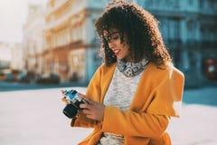 Gelockte brasilianische Frau, die Retro- Kamera verwendet Lizenzfreie Stockfotos