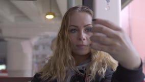 Gelockte Frau, die den Handy sitzt auf Sitz im Stadtpassagierbus schaut Rote behaarte Frau, die vorbei selfie Foto macht stock video footage