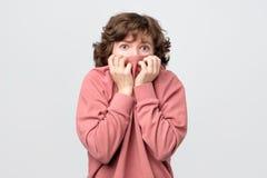 Gelockte Frau, die ihre Fingernägel sehnend für etwas oder besorgt beißt lizenzfreies stockbild