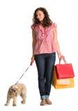 Gelockte Frau mit Einkaufstaschen und amerikanischem Spaniel Stockbilder
