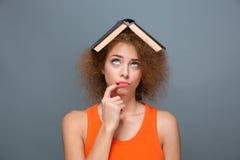 Gelockte gestörte Frau, die mit Buch auf Kopf lustig schaut Stockfoto