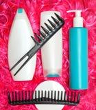 Gelockte Haarpflege- und anredenprodukte auf hellem rosa Puppenhaar Stockbilder