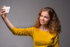 Gelockte junge Frau in der gelben Kleidung froh und mit einem Lächeln MA Lizenzfreie Stockfotografie