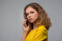 Gelockte junge Frau in der gelben Kleidung schlecht gelaunt sprechend auf Stockbilder