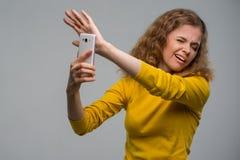 Gelockte junge Frau in der gelben Kleidung unglücklich mit ihrem Auftritt Stockbild