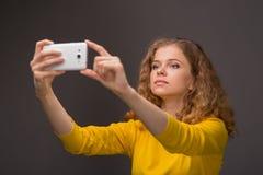 Gelockte junge Frau in der gelben Kleidung unglücklich mit ihrem Auftritt Lizenzfreie Stockfotos