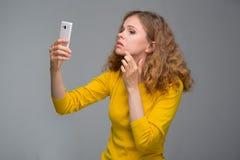 Gelockte junge Frau in der gelben Kleidung unglücklich mit ihrem Auftritt Stockbilder