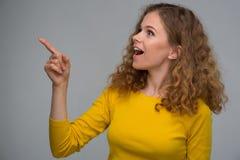 Gelockte junge Frau in der gelben Kleidung zeigt Finger auf die Seite an Lizenzfreie Stockfotografie