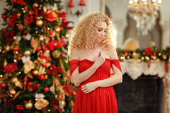 Gelockte schöne junge blonde Frau in einem roten Kleid auf Weihnachten Lizenzfreies Stockbild