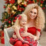 Gelockte schöne junge blonde Frau in einem roten Kleid umfasst daught Stockbild