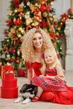 Gelockte schöne junge blonde Frau und eine Tochter in einem roten Kleid Lizenzfreie Stockfotos