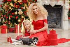 Gelockte schöne junge blonde Frau und eine Tochter in einem roten Kleid Lizenzfreie Stockbilder