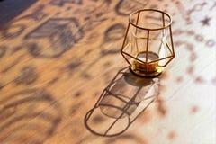 Gelockte Schatten auf einem Holztisch an einem sonnigen Tag, Designerkerzenständer, Nahaufnahme, selektiver Fokus, Kopienraum stockbilder
