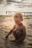 Gelockter blonder kleiner Junge sitzt auf dem Sand Lizenzfreies Stockfoto