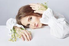 Gelockter blonder romantischer Blick, sch?ne Augen Wei?e Wildflowers in den H?nden Kleid des wei?en Lichtes des M?dchens und gelo lizenzfreie stockfotografie