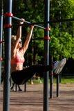 Gelockter blonder Sport des Bildes zieht auf Sportsimulator im Park hoch Lizenzfreies Stockbild