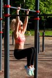 Gelockter blonder Sport des Bildes zieht auf Sportsimulator im Park hoch Lizenzfreie Stockfotos