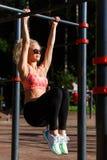 Gelockter blonder Sport des Bildes zieht auf Sportsimulator im Park hoch Stockbild