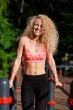 Gelockter blonder Sport des Fotos zieht auf Sportsimulator im Park hoch Stockfotos