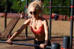 Gelockter blonder Sport des Fotos zieht auf Sportsimulator im Park hoch Lizenzfreies Stockbild