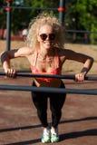 Gelockter blonder Sport des Fotos zieht auf Sportsimulator im Park hoch Lizenzfreie Stockbilder