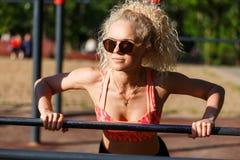 Gelockter blonder Sport des Fotos zieht auf Sportsimulator im Park hoch Stockbilder