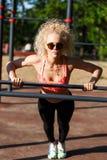 Gelockter blonder Sport des Fotos zieht auf Sportsimulator im Park hoch Lizenzfreies Stockfoto
