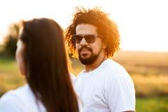 Gelockter dunkelhaariger junger Mann mit Bart in der Sonnenbrille betrachtet das Mädchen an einem sonnigen Tag lizenzfreie stockfotos
