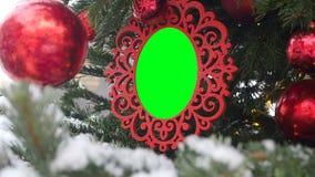 Gelockter geschnitzter Bilderrahmen, der am Tannen-Baum besprüht mit Schnee hängt Eingefügter grüner Farbenreinheits-Schlüssel in stock video footage
