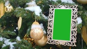 Gelockter geschnitzter Bilderrahmen, der am Tannen-Baum besprüht mit Schnee hängt Eingefügter grüner Farbenreinheits-Schlüssel in stock video