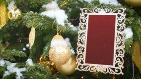 Gelockter geschnitzter Bilderrahmen, der am Tannen-Baum bespr?ht mit Schnee h?ngt Eingefügtes geschnitztes rotes Backgrounf in de stock footage