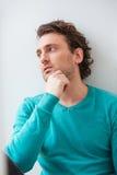 Gelockter nachdenklicher junger Mann, der das Fenster denkt und betrachtet Lizenzfreie Stockfotografie