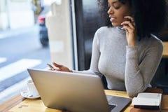 Gelocktes afro-amerikanisches in einer grauen Jacke unter Verwendung des freien drahtlosen Sitzens 5G im Café Lizenzfreie Stockfotos