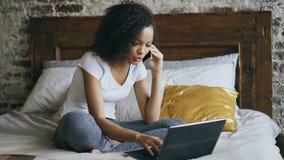 Gelocktes Afroamerikanermädchen Unterhaltungssmartphone und Anwendung der Laptop-Computers, die zu Hause im Bett sitzt stock footage