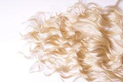 Gelocktes blondes Haar auf weißem Hintergrund Stockbild
