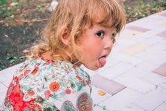 Gelocktes blondes Kind, das draußen im Sommer spielt Lizenzfreies Stockfoto