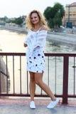 Gelocktes blondes Mädchen, das auf der Brücke steht und ein weißes Sca hält Stockfoto
